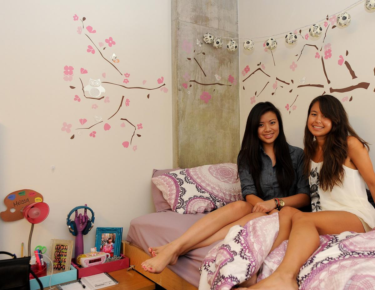 two roommates smile and sit on a bed together in front of a wall decorated with flowers and lantern lights