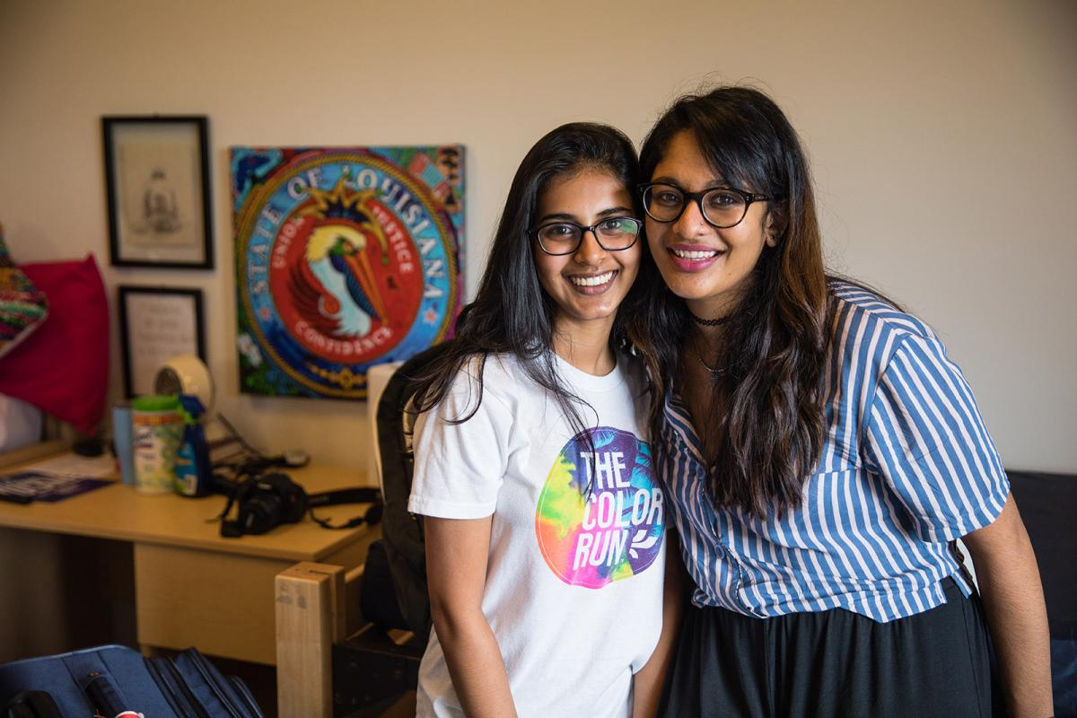 two roommates smile at the camera on move in day in their newly decorated room