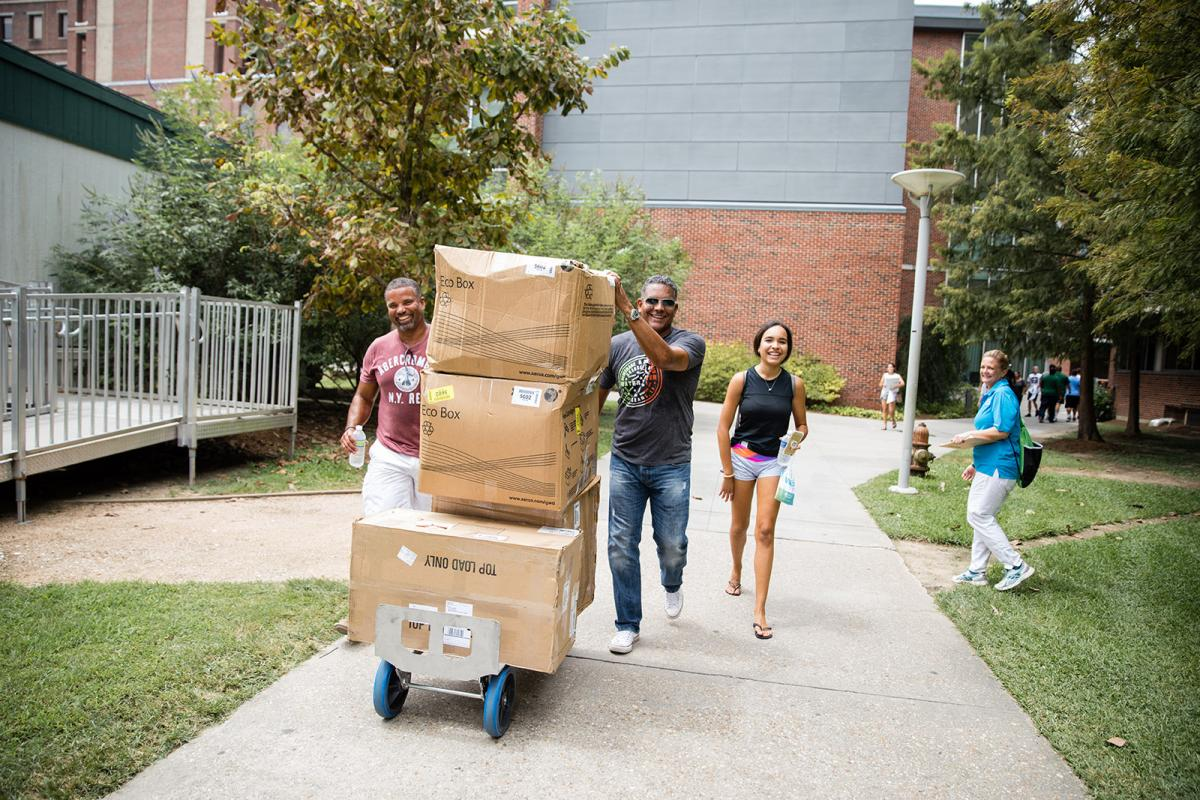 a student and two family members smile as they push a cart of boxes toward monroe hall on move in day
