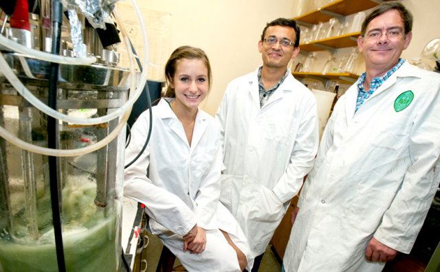 Three honors students in a chemistry lab wearing white coats and smiling