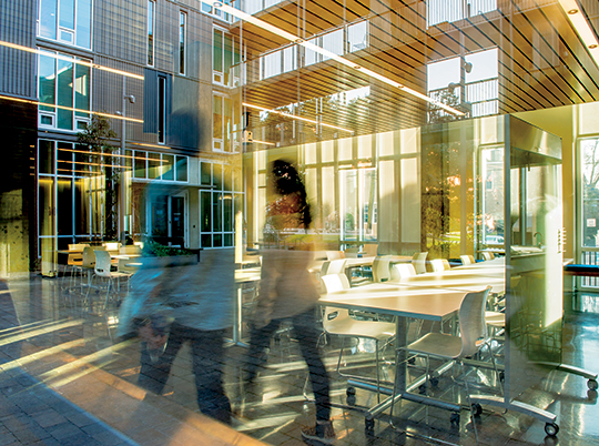 double exposure of students walking through greenbaum hall