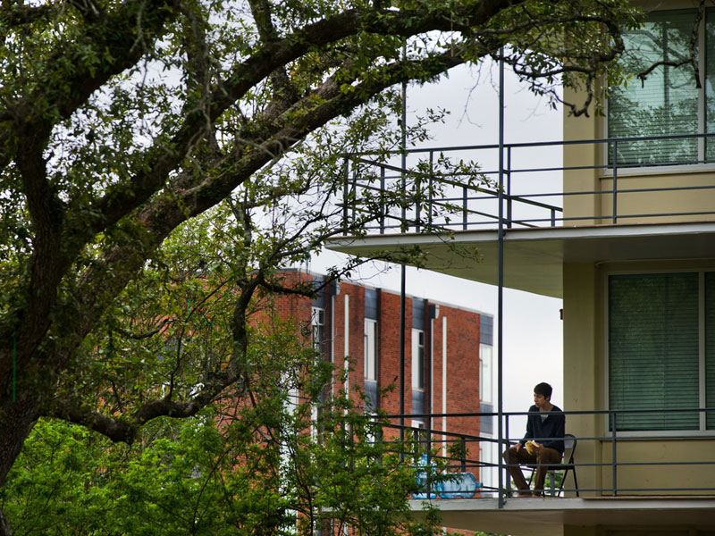 Student sits on balcony of residence hall