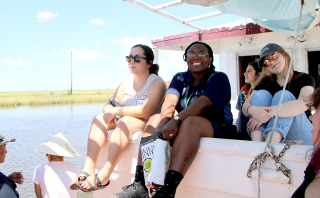 Third Coast students sit on a boat in a bayou and smile at the camera